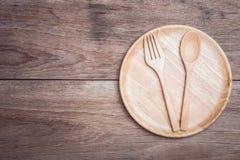 Plat et cuillère en bois sur la vue supérieure en bois de table Photographie stock libre de droits
