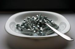 Plat et cuillère remplis de vis d'acier inoxydable photo libre de droits
