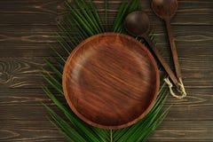 Plat et cuillères en bois avec la palmette sur le fond en bois brun Photo libre de droits