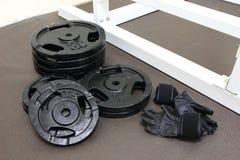 Plat et gants de poids de Barbells Photographie stock libre de droits