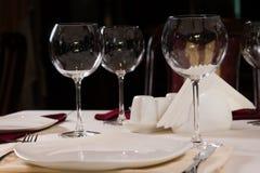 Plat et verres à vin vides sur une table de dîner Image stock