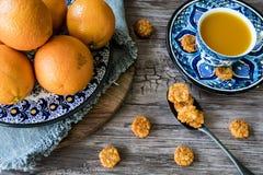 Plat fait main espagnol bleu avec des oranges, peau, jus d'orange, sur le fond en bois photos stock