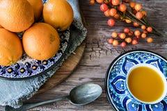 Plat fait main espagnol bleu avec les oranges, le jus et la cuillère d'argent sur la table en bois photos stock