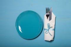 Plat, fourchette et couteau dans la serviette sur le fond en bois images stock