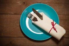 Plat, fourchette et couteau dans la serviette sur le fond en bois toned Photographie stock libre de droits