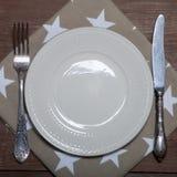 Plat, fourchette et couteau sur la serviette sur le fond en bois images libres de droits
