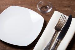 Plat, fourchette et couteau sur la serviette sur le fond en bois toned Image stock