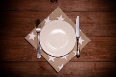 Plat, fourchette et couteau sur la serviette sur le fond en bois toned Photographie stock