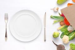 Plat, fourchette et knige vides sur la table avec des légumes dans le sac de papier à coté Photos libres de droits