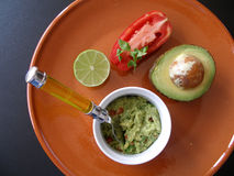 Plat of guacamole. Guacamole presented with tomato on an earthware plate royalty free stock photo