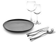 Plat noir avec des verres de vin de fourchette et de couteau Photo stock