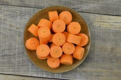 Plat noir avec les carottes coupées profondément sur le fond en bois photos stock