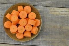 Plat noir avec les carottes coupées profondément sur le fond en bois photo stock
