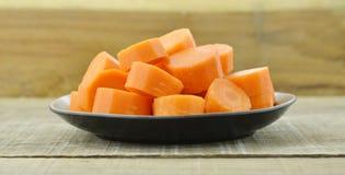 Plat noir avec les carottes coupées profondément sur le fond en bois photographie stock