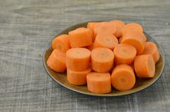 Plat noir avec les carottes coupées profondément sur le fond en bois, droite images libres de droits