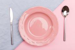 Plat rose sur les serviettes colorées avec la vue supérieure de couverts photo stock