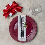 Plat rouge avec le boîte-cadeau, avec la fourchette, le couteau, le brunch du romarin et la serviette blanche au fond blanc photo libre de droits