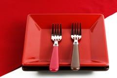Plat rouge et deux fourchettes sur un rouge Photos libres de droits