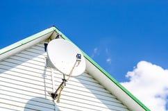 Plat satellite sur la maison Photo stock