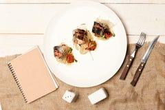 Plat sophistiqué de restaurant près de fourchette, de cuillère, de carnet, de sel et de poivre image libre de droits