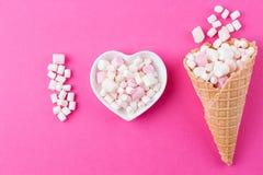 Plat sous forme de coeur avec une guimauve sur un fond rose Photo stock