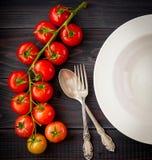 Plat sur une table en bois avec des tomates de groupe Photos libres de droits
