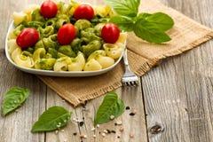 Plat traditionnel de pesto de basilic avec des tomates-cerises sur le bois rustique Photo libre de droits