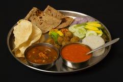 Plat typique de déjeuner de Maharashtrain avec le chapati, le jus ou les aamras de mangue, le riz, l'oignon et le légume image libre de droits