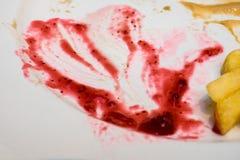 Plat vide après nourriture, restes rouges et jaunes de nourriture de sauce et f image libre de droits