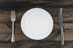 Plat vide avec le couteau de fourchette et de beurre sur la table en bois Image libre de droits
