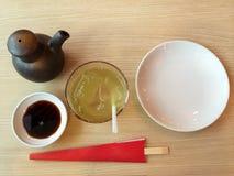 Plat vide, baguettes de sushi, sauce de soja et thé vert de glace sur la table en bois Images libres de droits