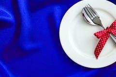 Plat vide blanc avec la fourchette et la cuillère et ruban rouge sur le luxe Photographie stock libre de droits