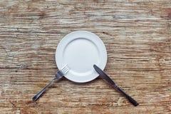 Plat vide blanc sur la table en bois Photos stock
