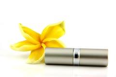 Plata las flores del amarillo y de la cubierta del lápiz labial. Imagen de archivo