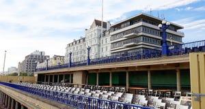 Plataforma com as cadeiras na costa de Eastbourne imagem de stock