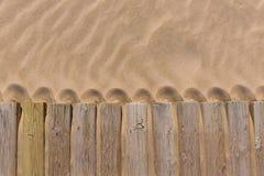 A plataforma da madeira de pinho resistiu na textura da areia da praia Imagens de Stock Royalty Free