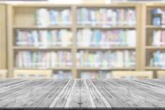 Plataforma de espacio vacía del tablero de madera con el fondo de la falta de definición de la biblioteca fotografía de archivo libre de regalías