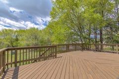 Plataforma de madeira com céus nebulosos e as árvores verdes fotografia de stock
