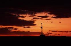 Plataforma de perforación en la puesta del sol Fotografía de archivo