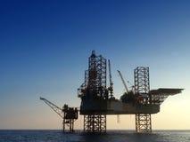 Plataforma de perfuração a pouca distância do mar da plataforma petrolífera da silhueta Fotos de Stock Royalty Free