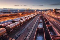 Plataforma del tren del cargo en la puesta del sol con el envase fotos de archivo