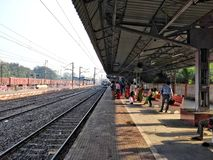 Plataforma e linha ferroviária indianas da estação de trem com os povos da multidão que esperam a chegada entrante do trem imagens de stock royalty free