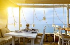 A plataforma e o sofá de madeira com os descansos do café grego tradicional na frente da praia ajardinam com opinião do mar Imagens de Stock Royalty Free