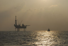 Plataforma petrolífera com o barco à espera no por do sol imagens de stock royalty free