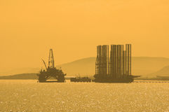 Plataforma petrolífera durante o por do sol em Caspi Fotos de Stock Royalty Free