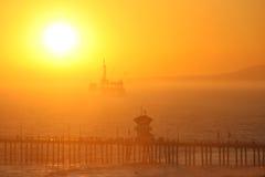 Plataforma petrolífera a pouca distância do mar no por do sol Imagem de Stock Royalty Free