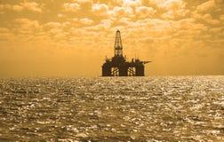 Plataforma petrolera durante puesta del sol en Caspi Imagen de archivo