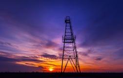 Plataforma petrolera perfilada en el cielo dramático de la puesta del sol Foto de archivo libre de regalías