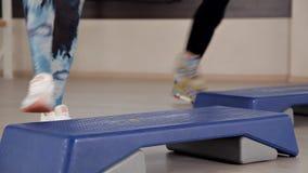 Plataformas da etapa Meninas nas sapatas dos esportes que fazem exercícios para a ginástica aeróbica O conceito do aperto no gym  video estoque