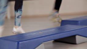Plataformas da etapa Meninas nas sapatas dos esportes que fazem exerc?cios para a gin?stica aer?bica O conceito do aperto no gym  filme